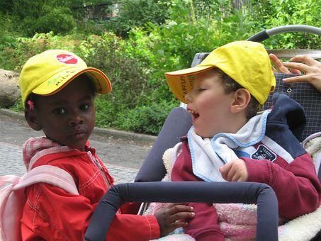 Zwei Kinder, eines  davon sitzt im Rollstuhl und das zweite, dunkelhäutige Kind, steht vor ihm